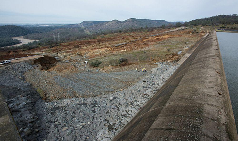 Специалисты оценивают разрушение аварийного водосброса после того, как уровень воды в озере немного упал.