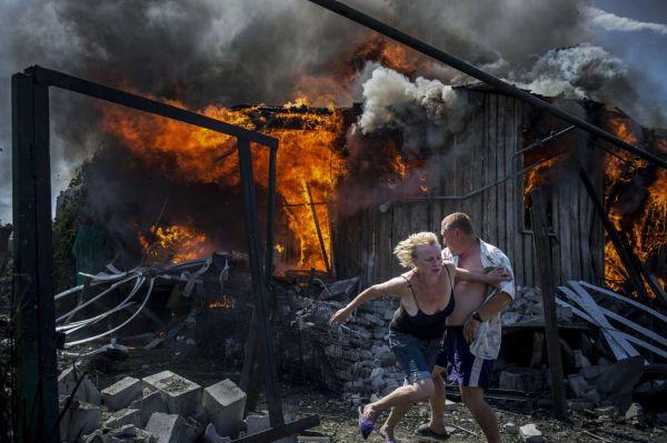 В категории «Долгосрочный проект» первое место заняло фото, которое было сделано у нас в Украине, в Луганской области. На фото видно, как жильцы сбегают от пылающего дома, который загорелся в результате артобстрела
