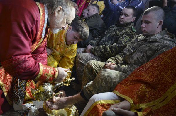 Символичное фото, на котором священнослужитель омывает ноги в день Страстного четверга украинскому защитнику
