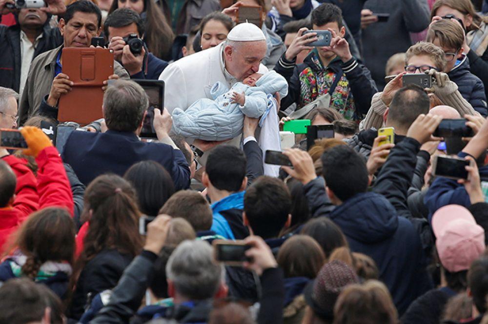 22 февраля. Папа Римский Франциск целует ребенка во время еженедельной аудиенции на площади Святого Петра в Ватикане.