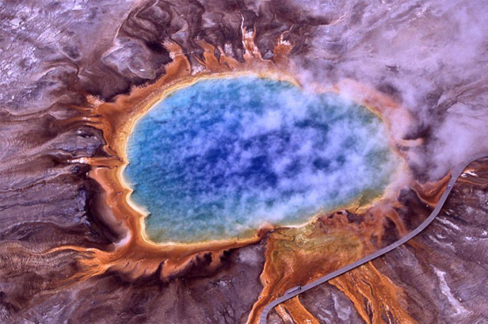 Большой призматический источник. Благодаря ярко окрашенным бактериям и водорослям дно мелкого озера, образовавшегося у выхода источника, переливается всеми цветами радуги.