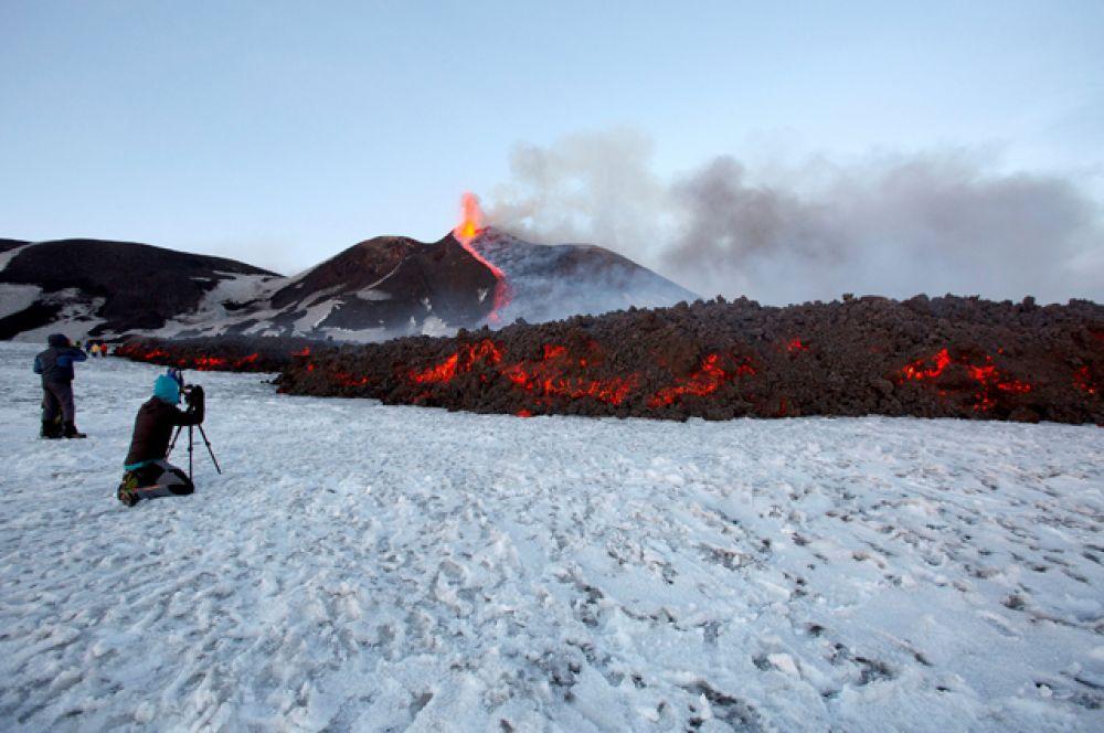 Туристы фотографируют застывающую лаву.