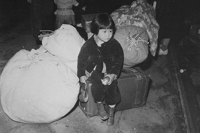 Японская девочка ожидает интернирования. США, весна 1942 года