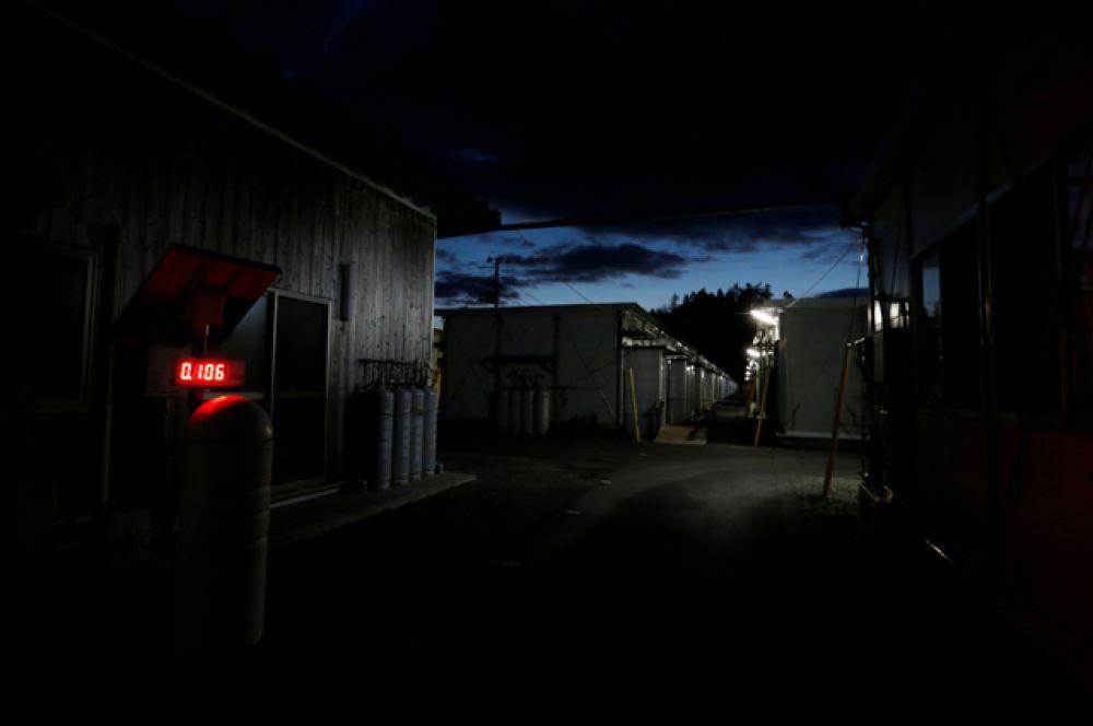 Временный жилой комплекс, где размещены эвакуированные из города Намиэ жители. Счетчик Гейгера, измеряющий уровень радиации, показывает 0,106 микрозиверт в час – безопасный уровень излучения.