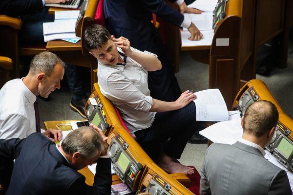 В первый день работы в Верховной Раде Савченко  пришла в классической рубашке и штанах. Все бы ничего, но депутат почему-то решила снять туфли и сидела на рабочем месте босиком