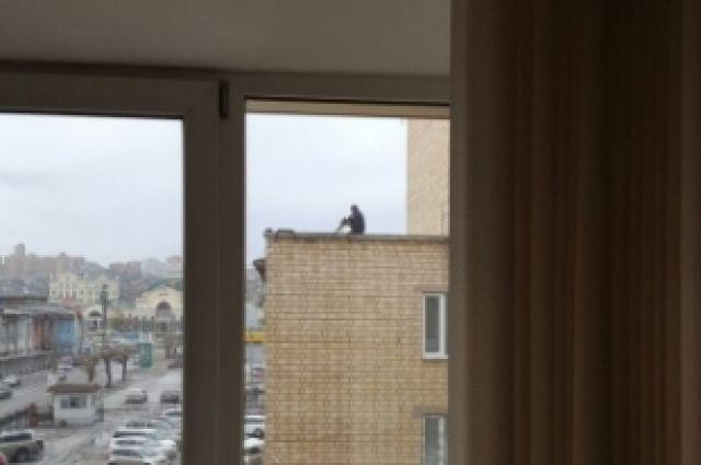 Мужчину, который находился на крыше общественного здания с оружием, по горячим следам задержали полицейские.