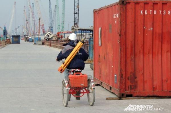 Некоторые строители ездят по рабочему мосту на велосипедах.