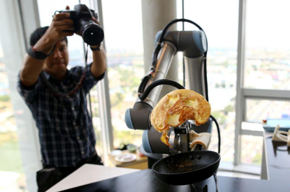 16 марта. В Бангкоке проходит выставка роботов. На фото: домашний робот готовит омлет.