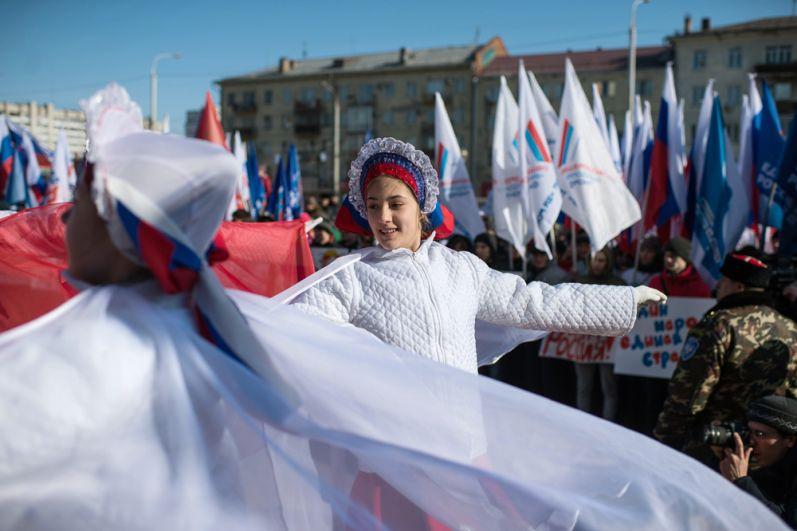 Участники представления во время митинга в честь третьей годовщины воссоединения Крыма с Россией у здания Пушкинской библиотеки в Омске.