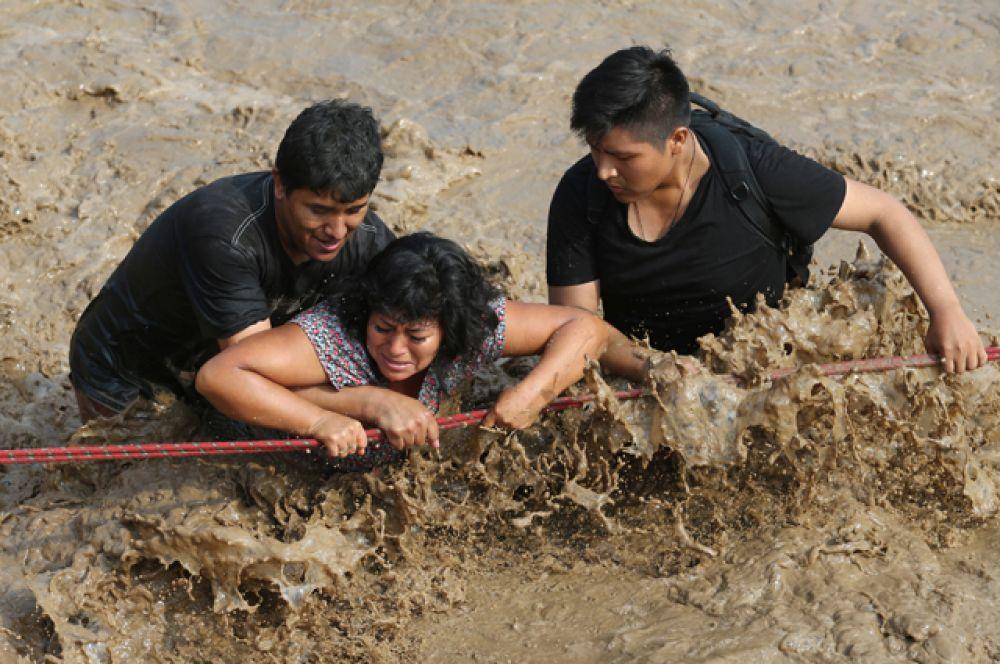 Лима. Полицейские помогают людям выбраться из затопленных районов.