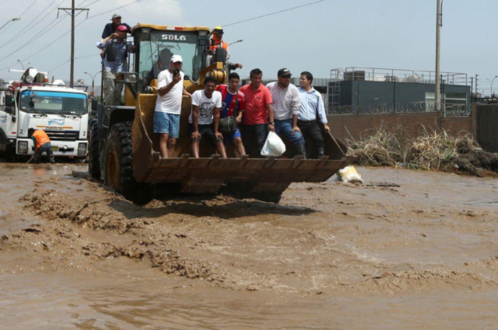 Экскаватор перевозит жителей после массивного оползня и наводнения в районе Уачипа в Лиме.