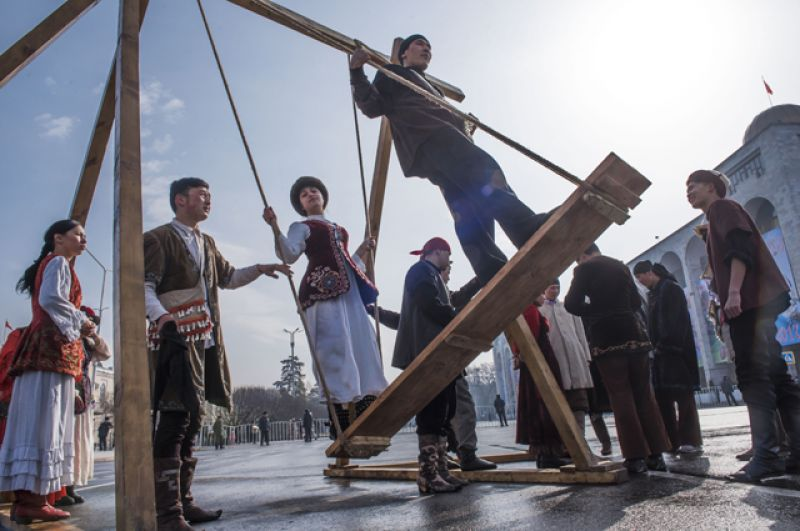 Молодые люди качаются на качелях на праздновании Навруза в Бишкеке.