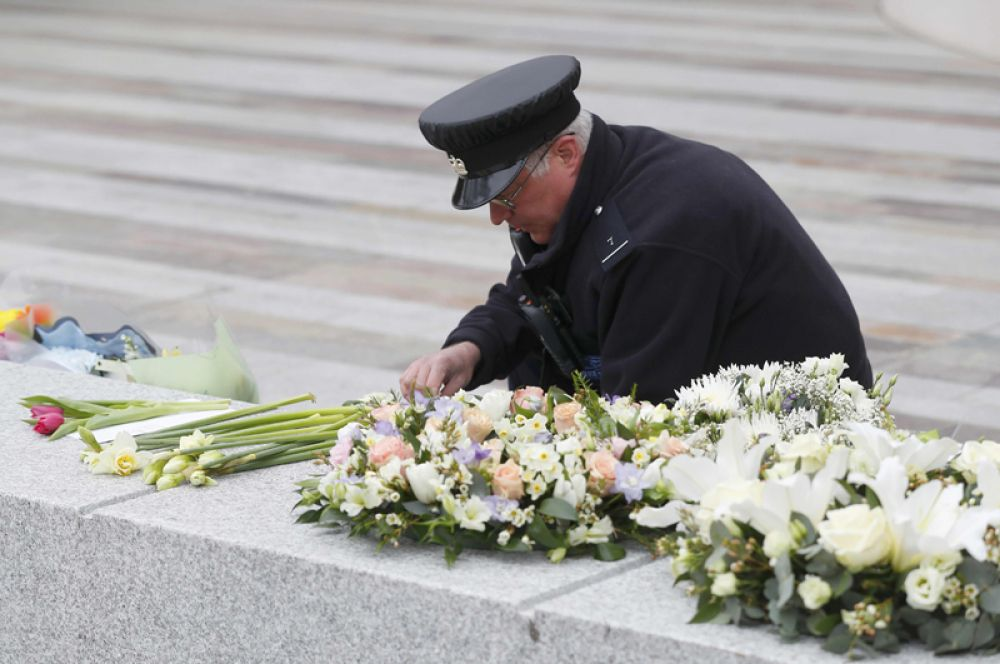 Сотрудник службы безопасности возлагает цветы в память о погибших.