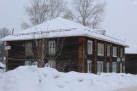 В городе началась оттепель, и снег падает с неочищенных крыш частных домов