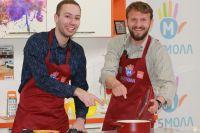 Олег Елисеев (справа) готовит рыбу.