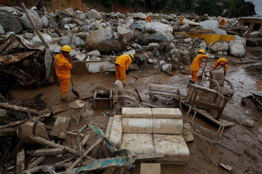 Спасатели ищут тела в разрушенном районе после наводнений и оползней.