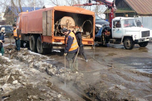 Канало-промывочная техника прочищает лоток ливневой канализации.