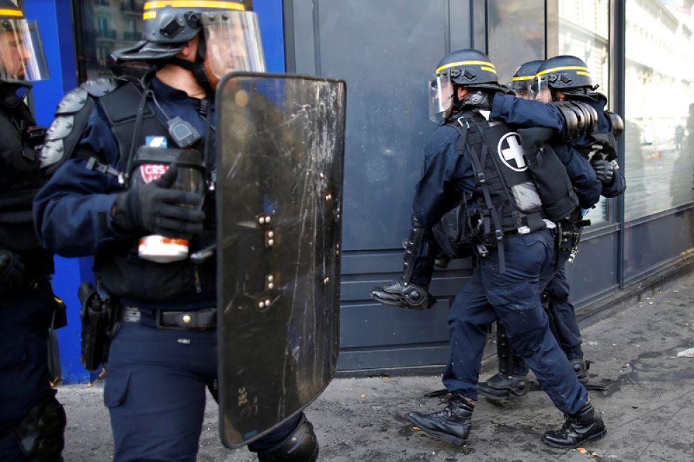 Стражи порядка уносят пострадавшего полицейского.