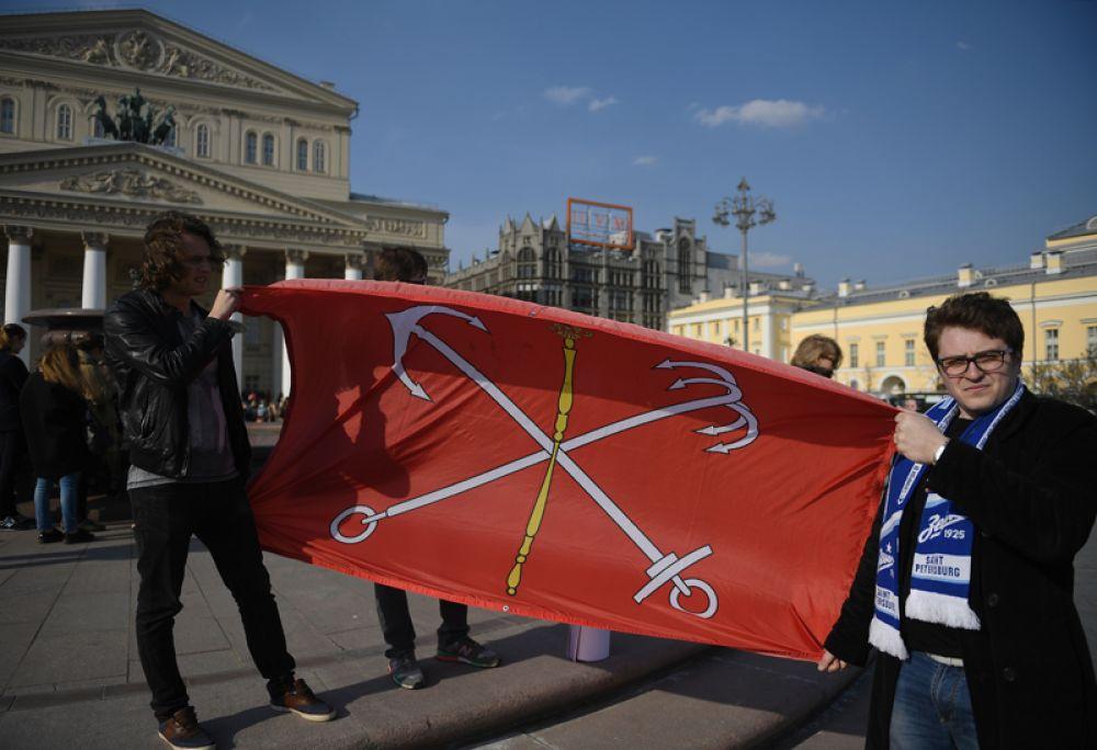 Участники акции памяти и солидарности «Питер — Мы с тобой!» в Москве держат флаг Санк-Петербурга.