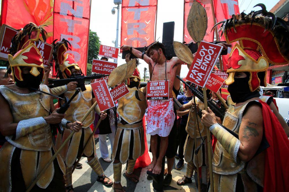 Актёры воспроизводят сцену распятия Иисуса Христа в знак протеста против многочисленных убийств в связи с антинаркотической кампанией Родриго Дутерте в Маниле, Филиппины.
