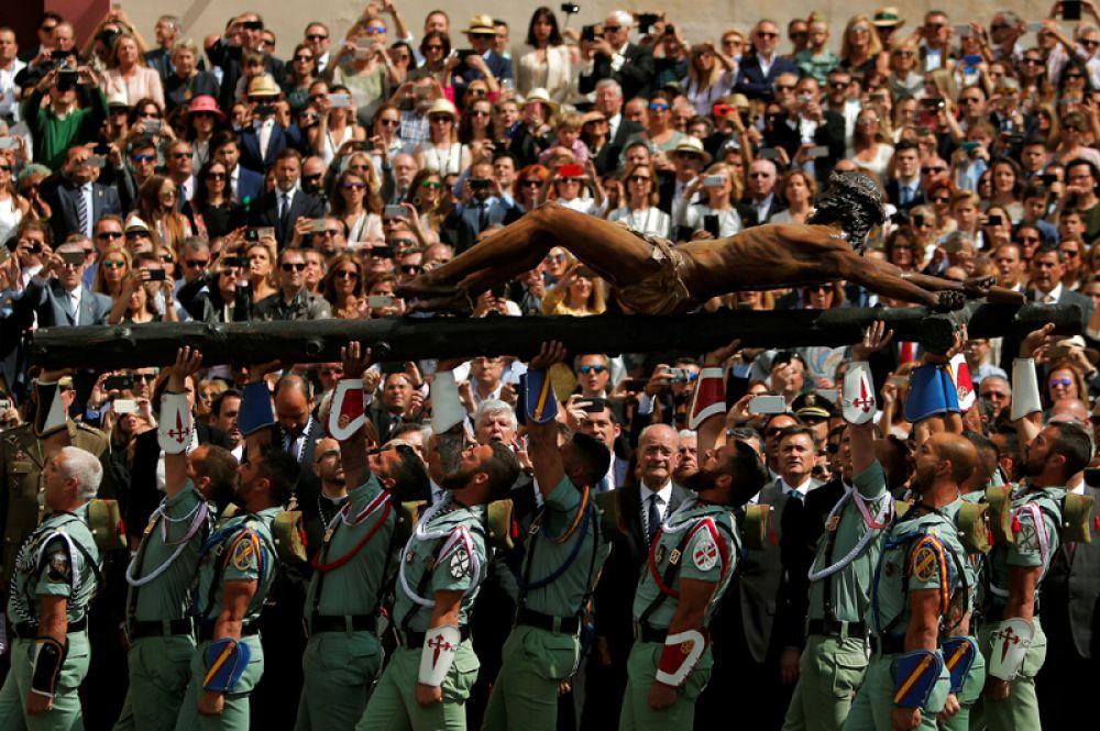 Испанские легионеры несут статую Христа во время церемонии, приуроченной к Страстной недели в Малаге, Испания.