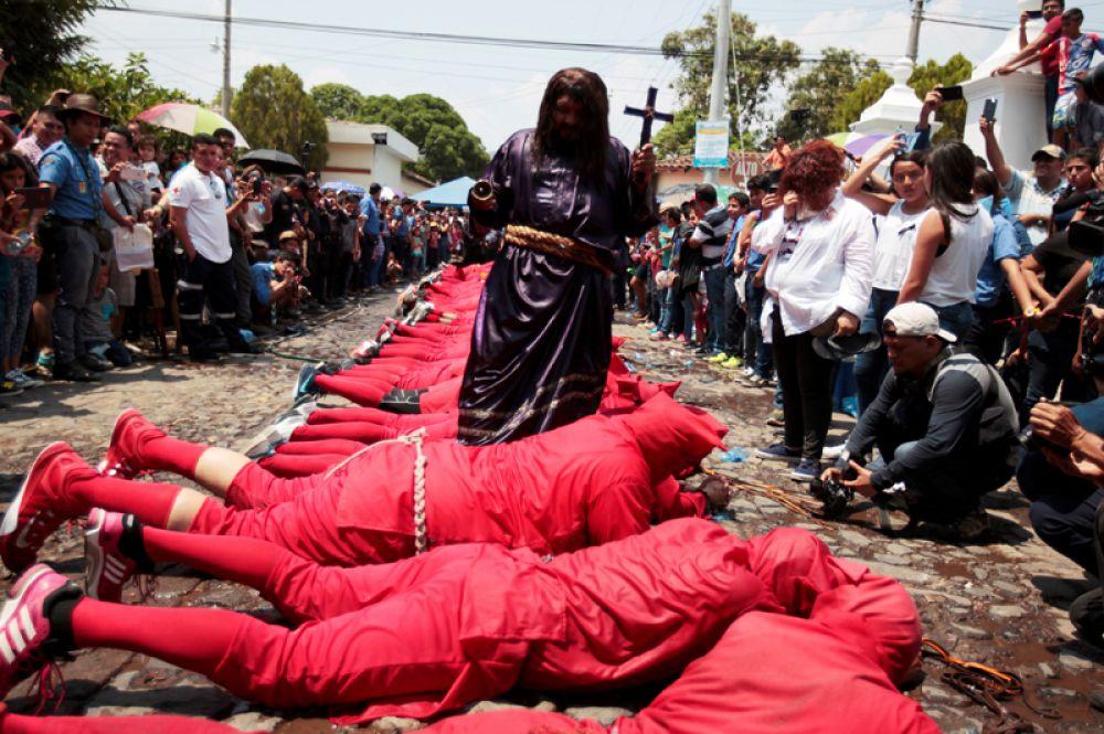 Верующие в костюмах дьявола и Иисуса Христа принимают участие в праздновании начала Страстной недели в Тексистепеке, Сальвадор.