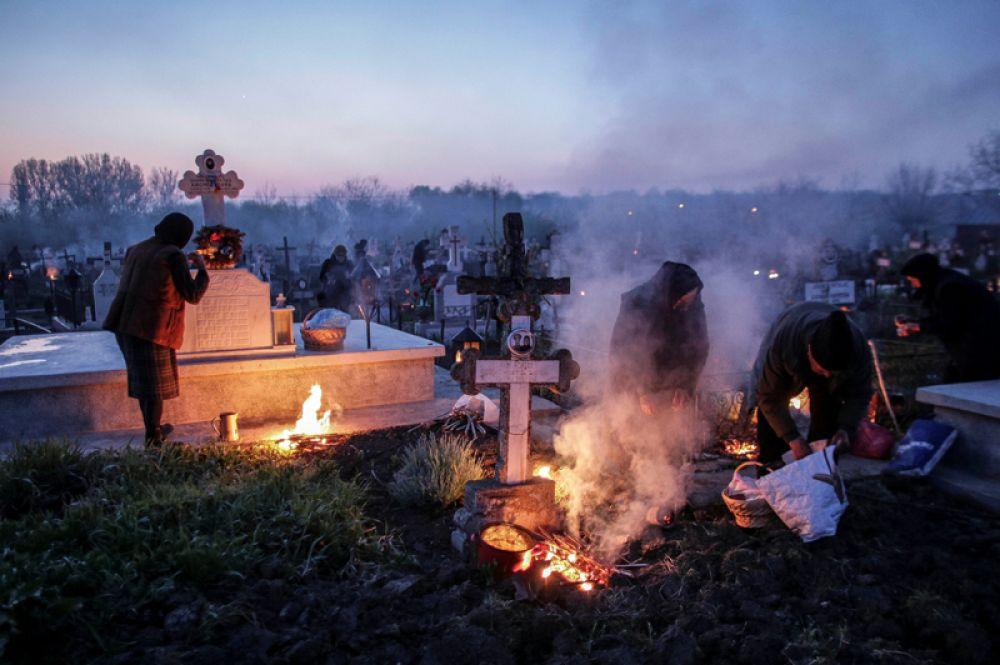 Люди зажигают огни и благовония возле могил родственников на кладбище в первые часы Великого Четверга, Румыния.