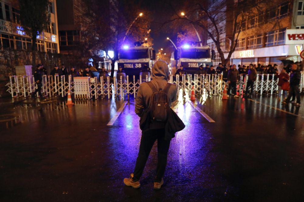 Противник реформы стоит перед полицейской баррикадой на главной дороге, ведущей к зданию Высшего избирательного совета в Анкаре.