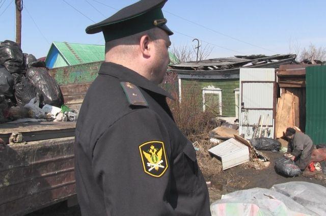 ВОмске судебные приставы чистят отмусора двор пенсионерки