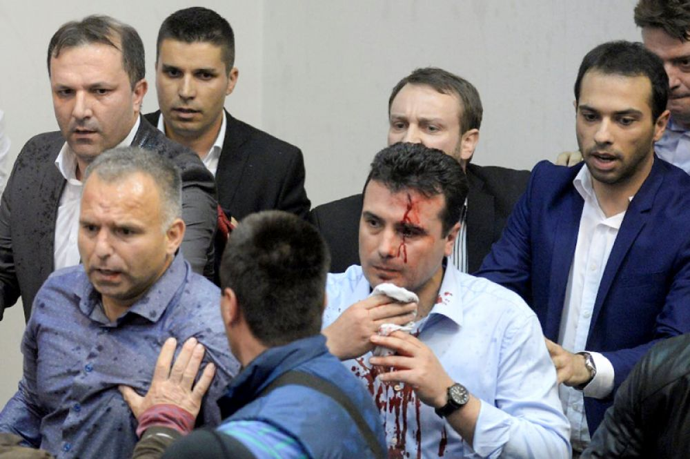 Пострадавшего лидера социал-демократов Зорана Заева сопровождают на выходе из парламента в Скопье.