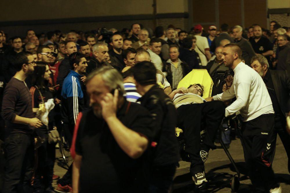 Демонстранты несут раненого после столкновений с ОМОНом возле парламента в Скопье.