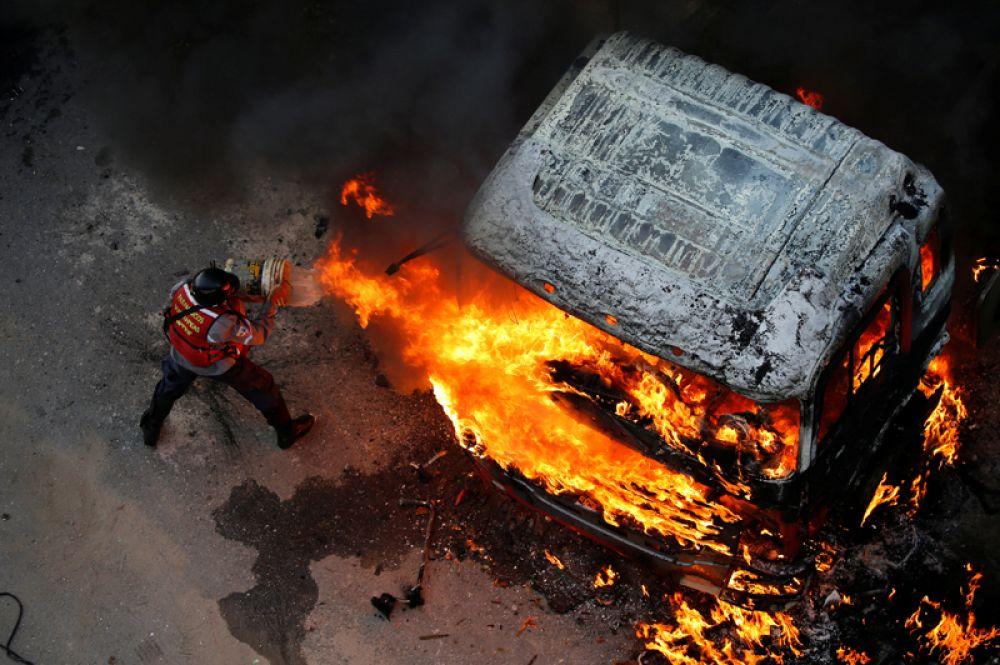 24 апреля. Пожарный пытается затушить пожар во время митинга против президента Венесуэлы Николаса Мадуро в Каракасе.