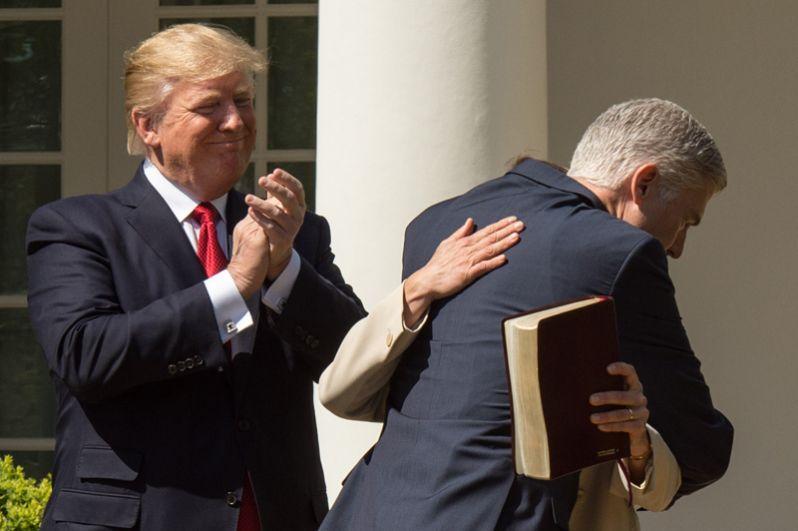 10 апреля. Дональд Трамп наблюдает за верховным судьёй США Нилом Горсачем, как тот обнимает свою супругу после принятия присяги в Розовом саду Белого Дома.