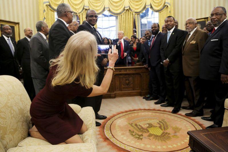 27 февраля. Советник президента Келлиэнн Конуэй фотографирует Дональда Трампа и руководителей ВУЗов, созданных для обучения афроамериканцев, во время встречи в Овальном кабинете Белого дома.