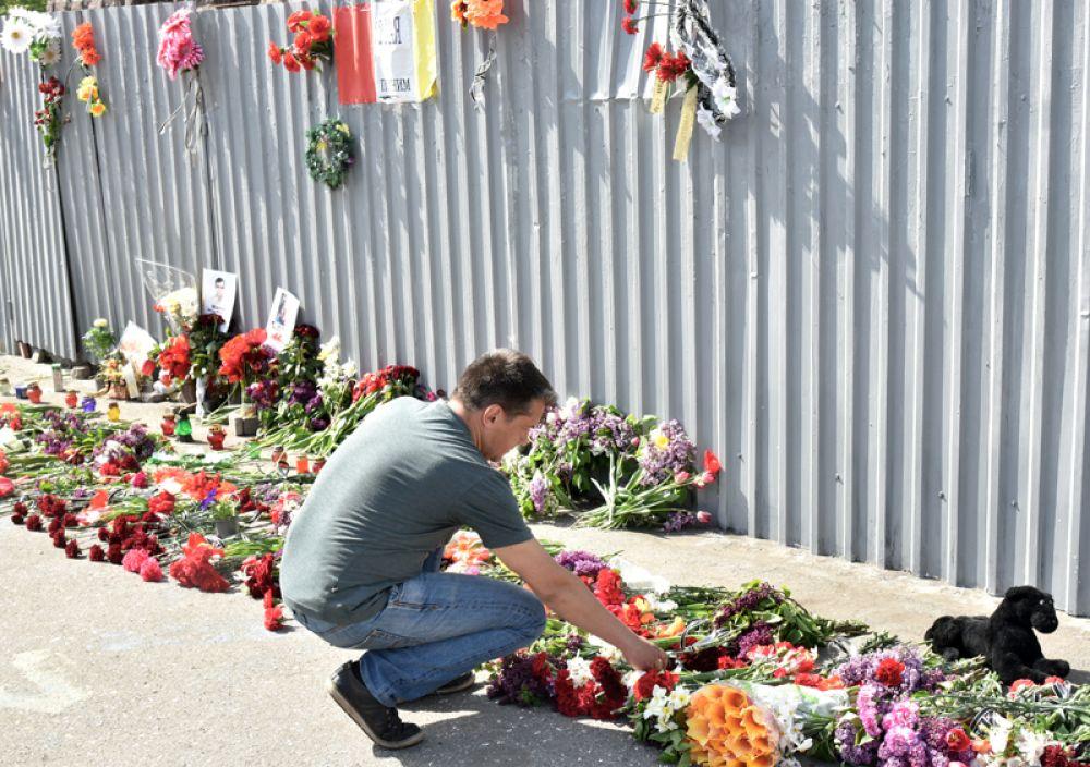 Мужчина возлагает цветы во время акции в память о погибших при пожаре в Доме профсоюзов на площади Куликово поле в Одессе.