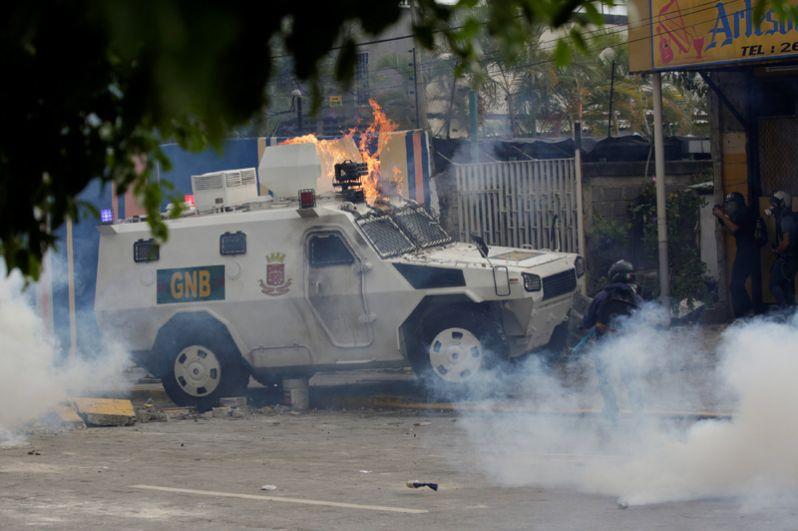 Горящий автомобиль полиции во время митинга против президента Николаса Мадуро в Каракасе.