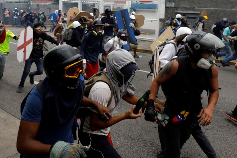 Столкновения оппозиционеров с полицейскими во время митинга против президента Николаса Мадуро в Каракасе.