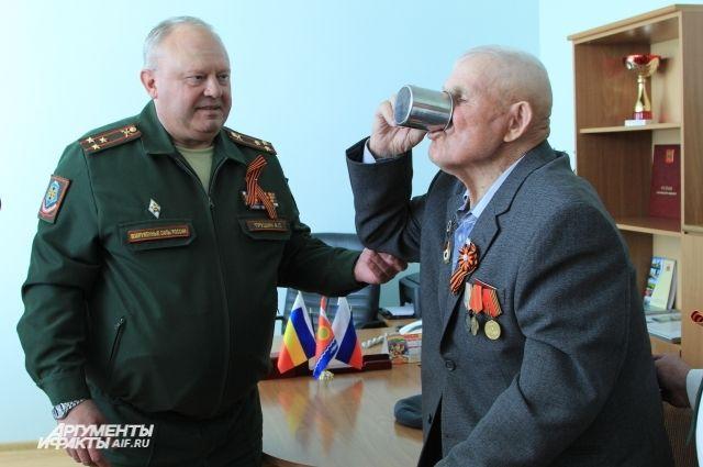 Пулемётчик Алексей Тихомиров обмывает орден, который он должен был получить в 1945 году.