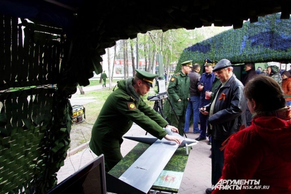 Военный показывает гостям праздника модель радиоуправляемого самолета разведки