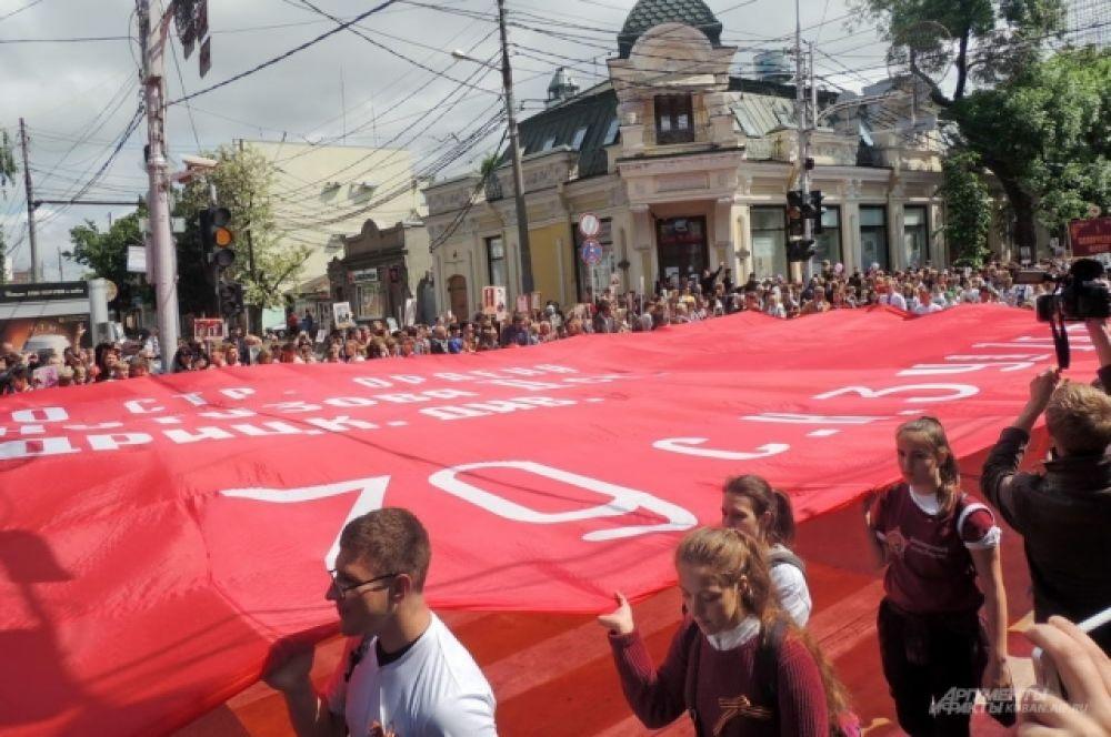 Участники шествия несли огромную копию Знамени Победы.