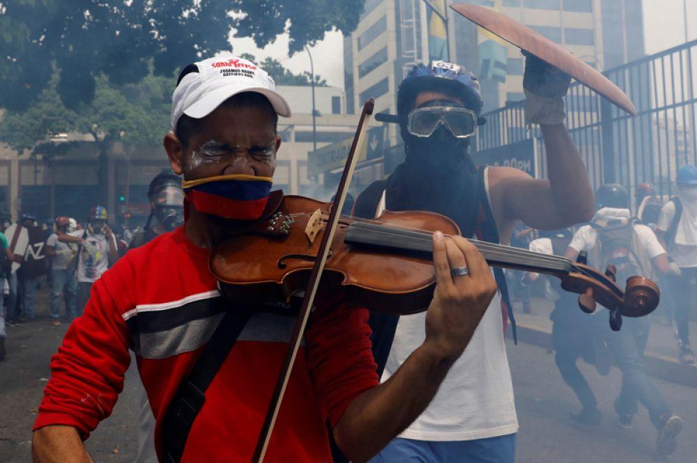 8 мая. Участник митинга против президента Николаса Мадуро в Каракасе играет на скрипке.