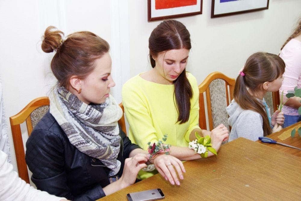 Молодые девушки тренировались в создании браслета из цветов на руку для невесты.
