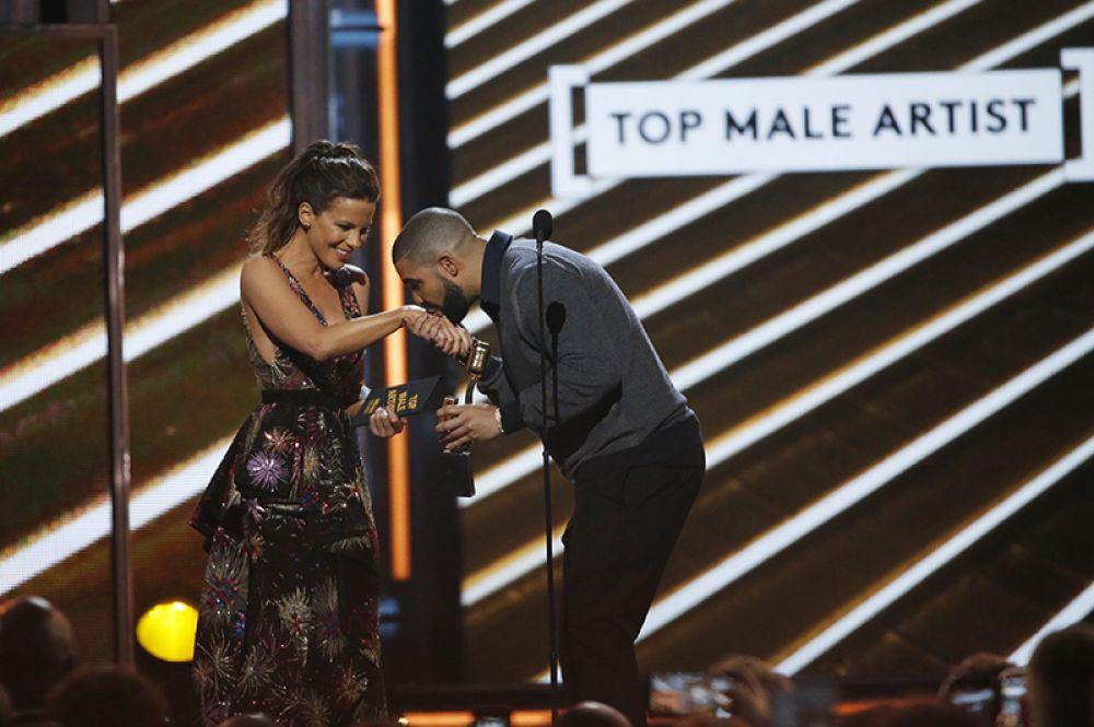 Дрейк принимает награду от актрисы Кейт Бекинсейл.