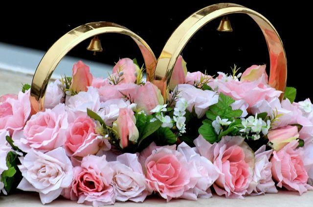 Молодой человек встал на одно колено и протянул своей возлюбленной букет роз и коробочку с обручальным кольцом.