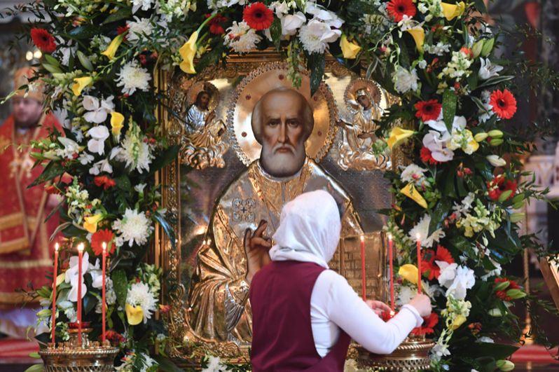 Женщина зажигает у свечи у иконы святителя Николая Чудотворца в храме Христа Спасителя, где находится ковчег с его мощами.