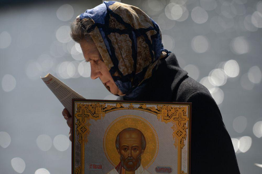 Верующая стоит в очереди к храму Христа Спасителя, где находится ковчег с мощами святителя Николая Чудотворца.