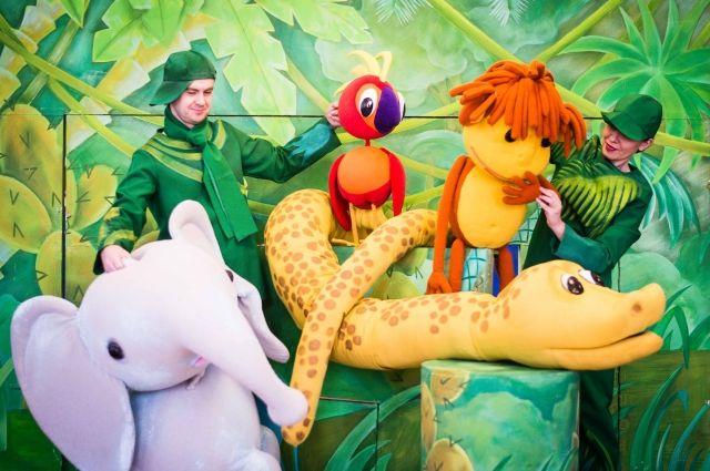 Ведомые кукольными персонажами спектакля «38 попугаев», участники представления весело прошествуют из первой очереди торгового центра во вторую.