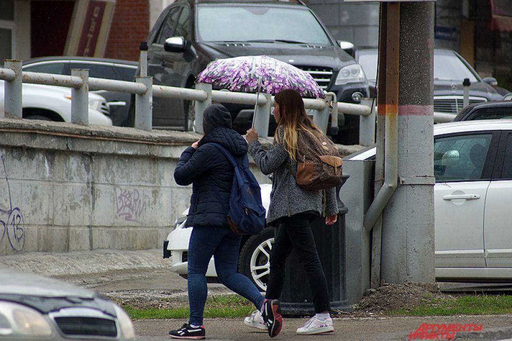На улицах можно было увидеть людей с зонтиками.