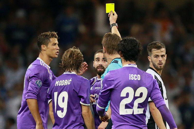 Главный судья матча Феликс Брих показывает жёлтую карточку игроку ФК «Реал Мадрид» Даниэлю Карвахалю (в центре).