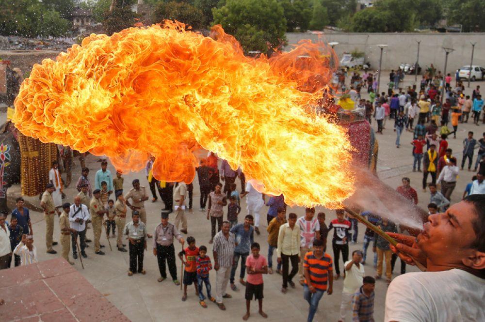 9 июня. Укротитель огня во время процессии Джал-Ятра перед ежегодной Рат-Ятрой в Ахмадабаде, Индия.